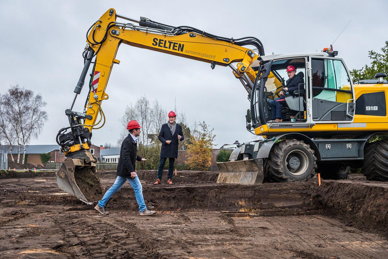 Wethouder Jan Goijaarts nam plaats in de graafmachine. Jan van Vucht, directeur-bestuurder van Area en Mike Janssen, uitvoerder van het project aan de Spoorlaan  moedigen hem aan.