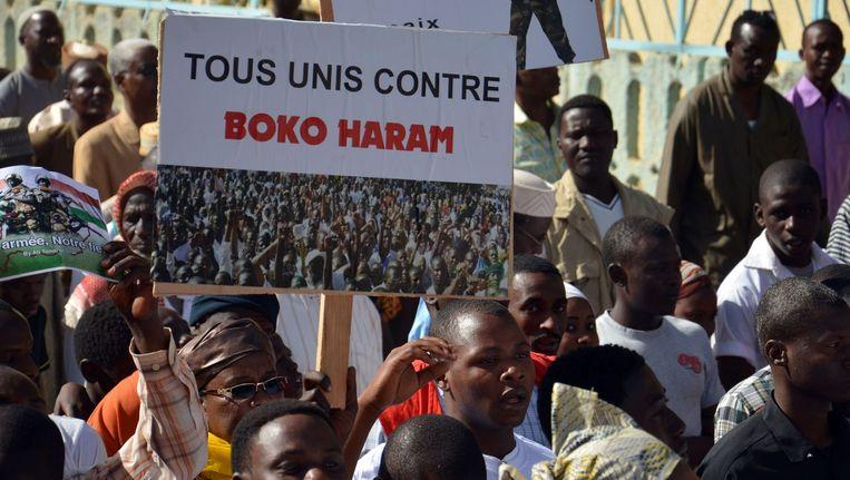 Een persoon houdt tijdens een demonstratie op 17 februari 2015 in Niamey een bord vast waarop staat 'allemaal verenigd tegen Boko Haram'. Beeld afp
