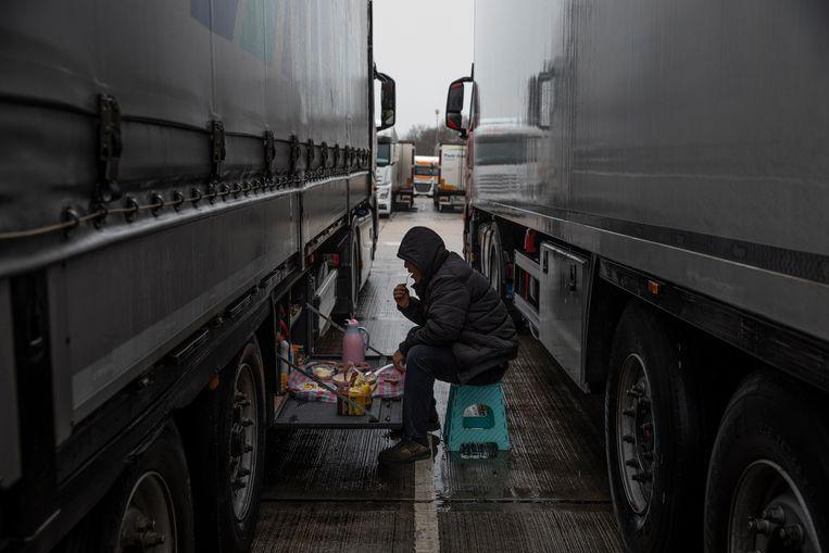 Een trucker ontbijt maandagochtend bij zijn vrachtwagen op een parking in de Britse havenstad Dover. Net als honderden collega's is hij gestrand. Beeld Getty Images