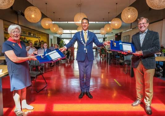 Burgemeester Harald Bergmann reikt de lintjes uit aan Ger van Waegeningh en Wim Jansen.