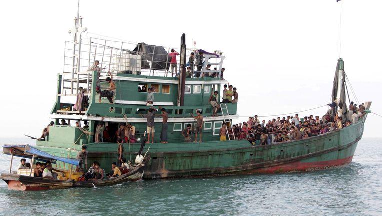 Migranten die al drie maanden op zee dobberden wachten op de vissersboot, voordat ze naar de kust worden gesleept. Beeld reuters