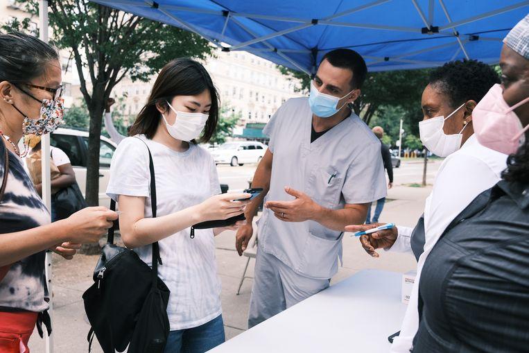 New Yorkers schrijven zich in voor een prik bij een mobiel vaccinatiecentrum. Beeld Getty Images