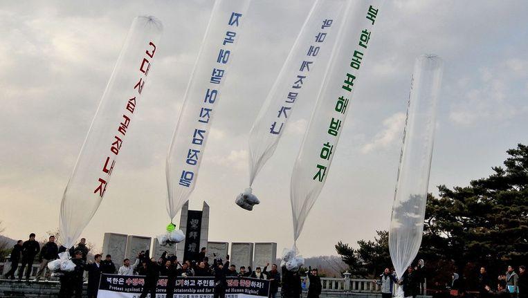 Vluchtelingen laten ballonnen met leuzen tegen het regime in Noord-Korea op aan de grens. Beeld epa