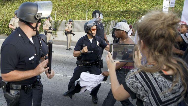 Politie in Los Angeles probeert bij snelweg 10 een aantal demonstranten tegen te houden. Beeld AFP