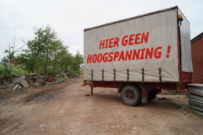 Varkenskweker Francky Snaet heeft op zijn bedrijf een aanhangwagen staan met het opschrift 'Hier geen hoogspanning'. De aanhangwagen staat naast de E403.