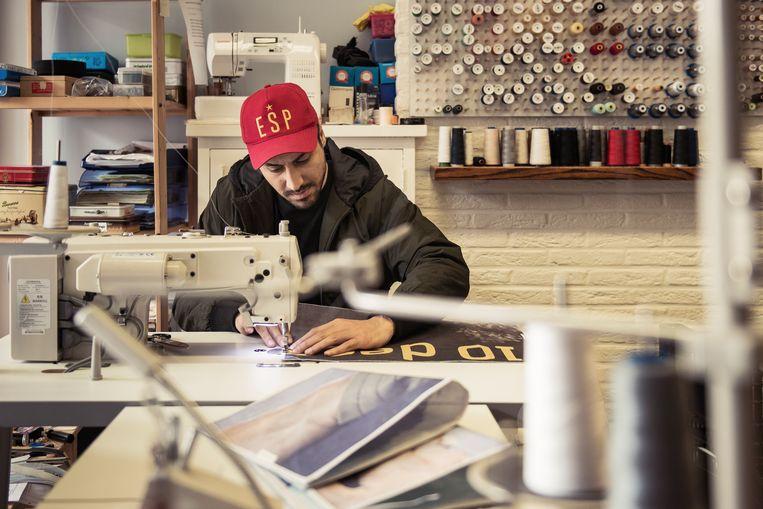 In het naaiatelier werken erkende vluchtelingen uit onder meer Irak, Syrië en Afghanistan.Ze maken schoolkledij omdat uniformen vaak zo duur zijn, doen retouches en zijn sinds kort begonnen met een upcycling-project waarbij ze bijvoorbeeld handtassen maken van oude jeans.   Beeld Tim Coppens