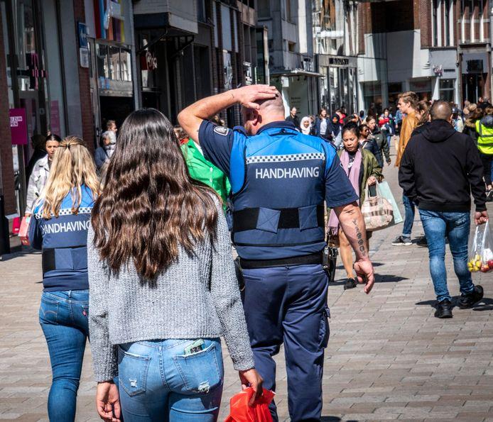 Handhavers van de gemeente in de Tilburgse Heuvelstraat, zaterdagmiddag.