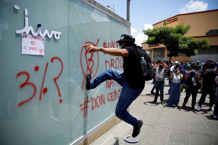 Demonstranten trappen in op een kiosk waar bitcoins gewisseld kunnen worden tijdens een protest tegen de overheid in San Salvador.  Beeld EPA