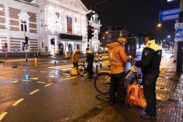 Politie handhaaft de avondklok op het Museumplein in Amsterdam. Beeld ANP
