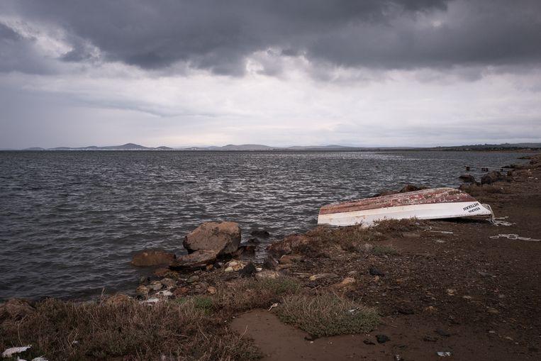Een bootje op het strand Badavut bij het Turkse stadje Ayvalik. Aan de overkant is het Griekse eiland Lesbos te zien, de bestemming van de migranten. Beeld Nicola Zolin