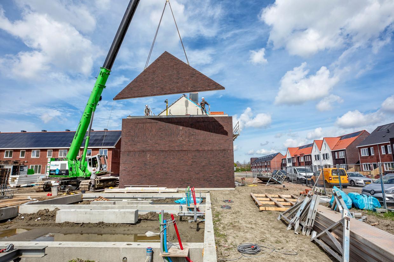 Met de kraan worden dakdelen op een woning in deMiddelburgse wijk Mortiere gehesen.  Beeld Raymond Rutting / de Volkskrant