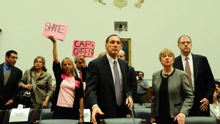 2008: actievoerders houden protestborden omhoog op het moment dat Richard S. Fuld Jr., topman van Lehman Brothers, zich opmaakt om te getuigen bij een hoorzitting in Washington over de val van zijn bank. Die leidde de wereldwijde financiële crisis in. Beeld AFP