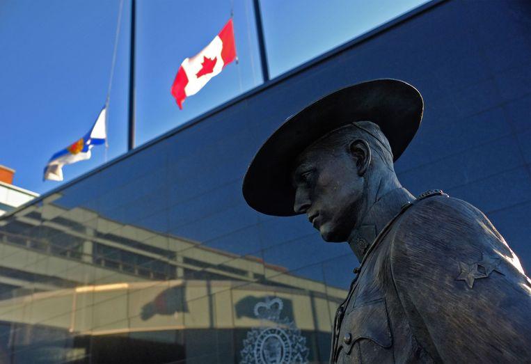 De vlaggen van Nova Scotia, de provincie waar Portapique ligt en de Canadese vlag hangen beide half stok bij het politiebureau in Dartmouth. Beeld AFP