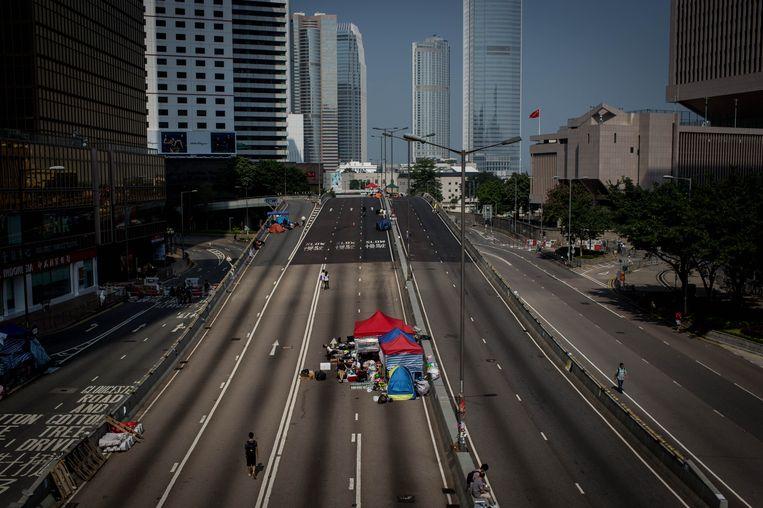 Een handjevol demonstranten bij regeringsgebouwen in Hongkong. Beeld Getty Images