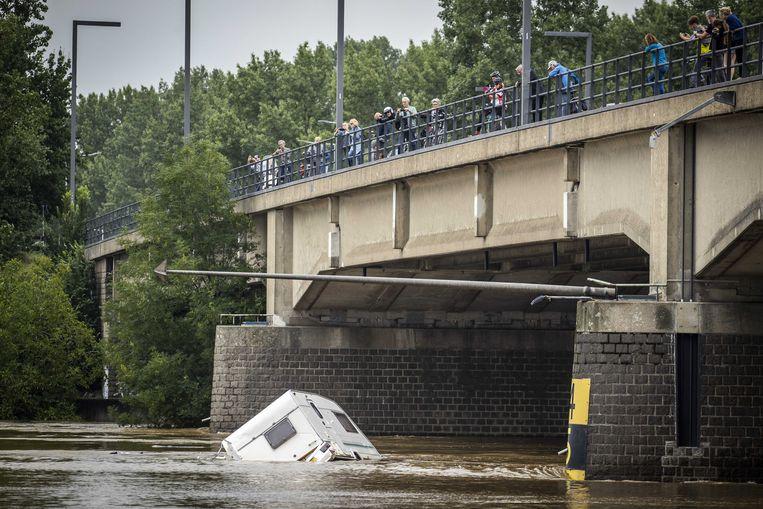Omstanders fotograferen vanaf een brug over de Maas bij Roermond een caravan die wordt meegesleurd door het water. Beeld ANP