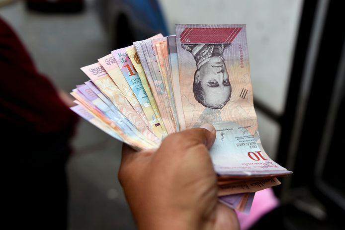 Un homme tient une liasse de bolivars, la devise vénézuélienne (Caracas, Venezuela, archives)