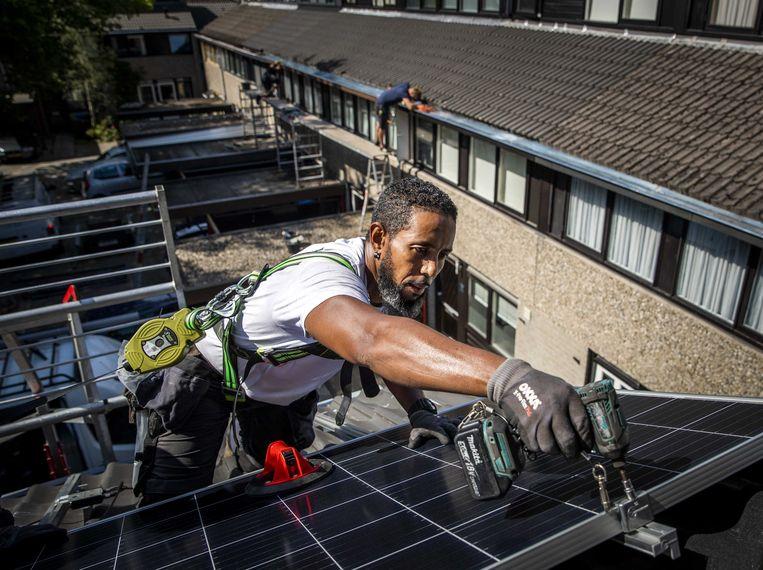 Een installateur plaatst zonnepanelen. Vlamingen kunnen vanaf 2021 geen aanspraak meer maken op de terugdraaiende teller. Beeld ANP