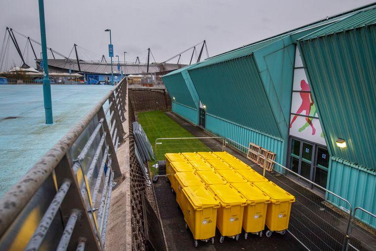 Klinische afvalbakken staan klaar bij het 'Manchester Tennis and Football Centre', dat binnenkort zal dienen als vaccinatiecentrum.    Beeld Getty Images