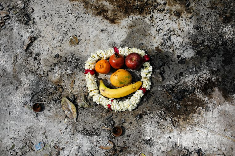 De plek waar een aan Covid-19 overleden persoon is gecremeerd, wordt gemarkeerd met een bloemenslinger en wat fruit. Het is onderdeel van een ritueel in een crematorium in New Delhi, India.  Beeld REUTERS