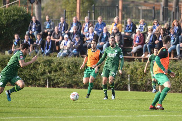 De Graafschap-aanvoerder Ralf Seuntjens stuurt Daryl van Mieghem (links) de diepte in tegen Europa FC. Op de achtergrond kijken sponsoren van de Doetinchemse club toe.