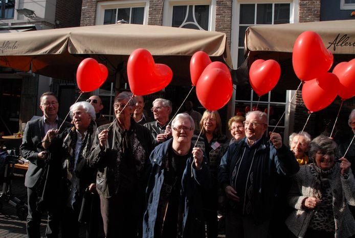 Een groepje ouderen staat klaar om hartjesballonnen de lucht in ter sturen, een symbolische handeling om de eenzaamheid te verjagen