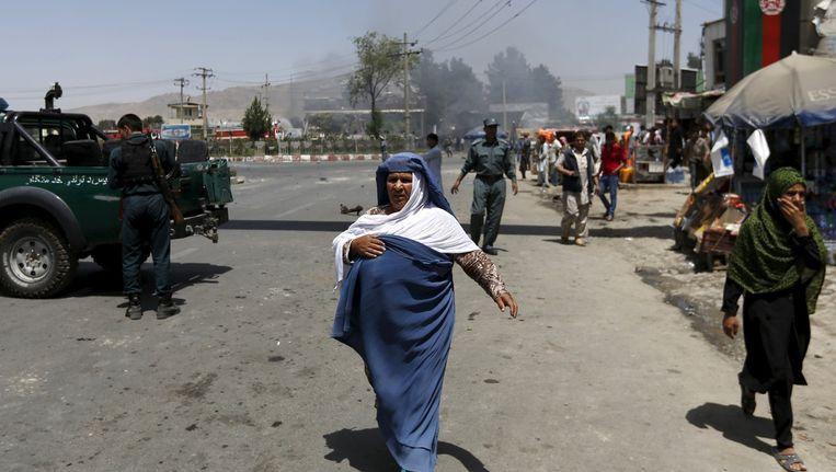 Een vrouw loopt weg van de plek waar een zelfmoordaanslag heeft plaatsgevonden, bij de ingang van het vliegveld in Kabul. Beeld reuters