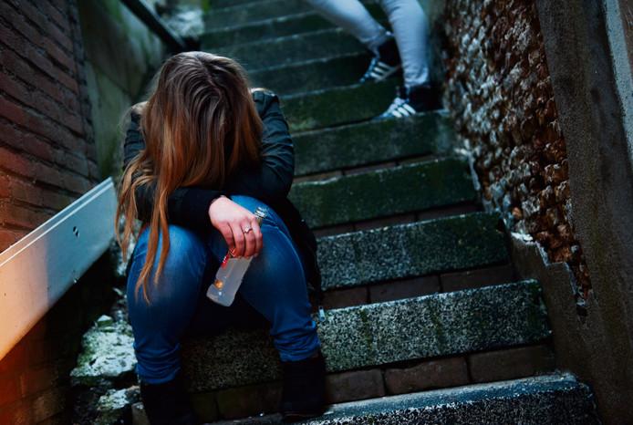Een meisje zit dronken op straat.