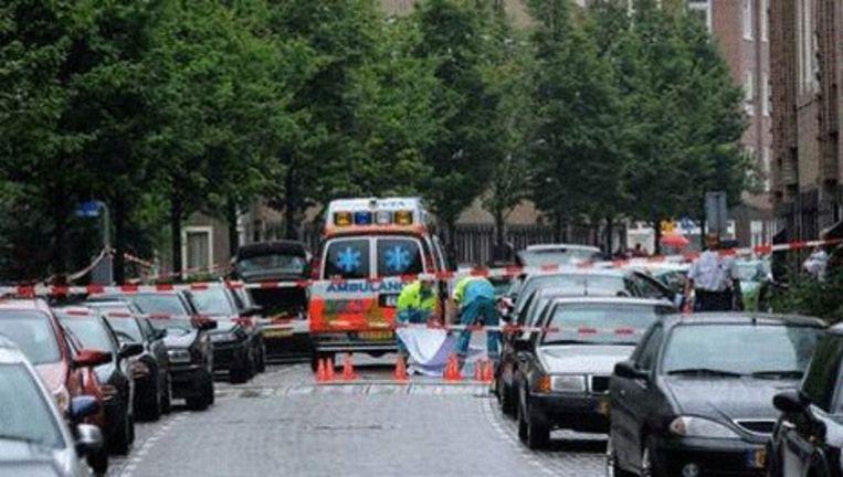 Ambulancepersoneel bedekt het lichaam in de Bestevaerstraat. Beeld