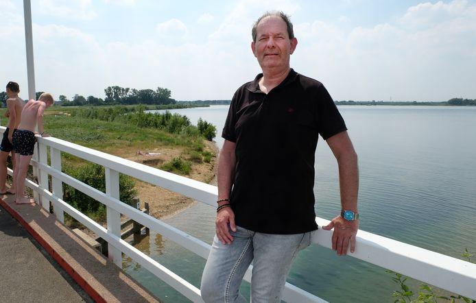 Projectleider Henk van Eldijk, op de witte ophaalbrug tussen Beers en Linden bij de Kraaijenbergse Plassen. Op onder meer de braakliggende grond achter hem wil TopParken een groot vakantiepark bouwen.
