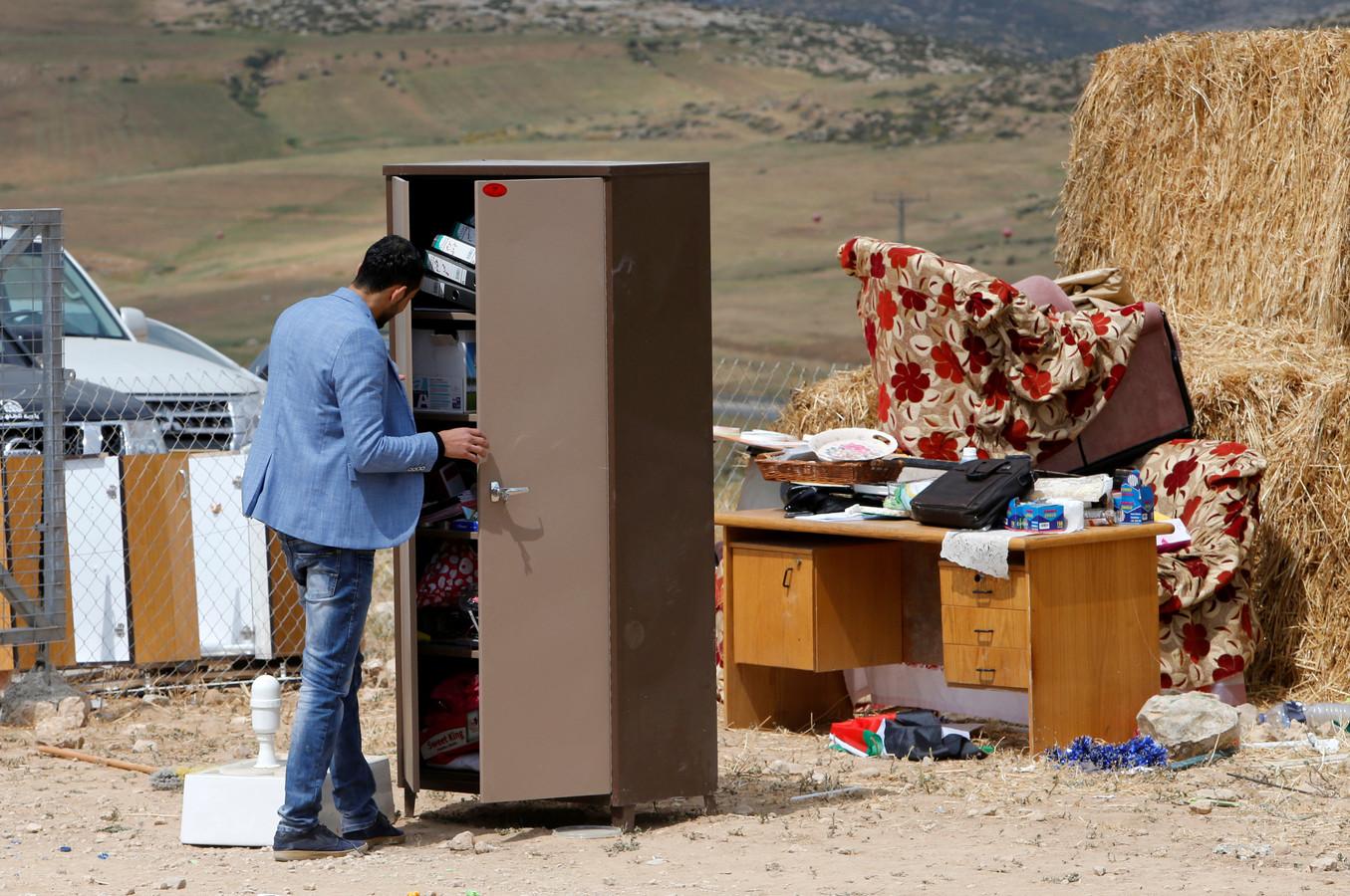 Een Palestijnse leraar bij een kast op de plek waar een school heeft gestaan.  Israëlische troepen verwijderden de muren en het dak van deze school op de bezette Westbank. Foto Mussa Qawasma