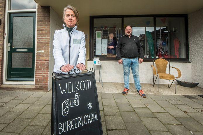 Initiatiefnemer Paula Kakkenberg (l) met vrijwilliger/bezoeker Thomas Bernard voor de laatste tijdelijke locatie van Het Burgerlokaal. Door het raam kijkt bezoeker Herma toe.