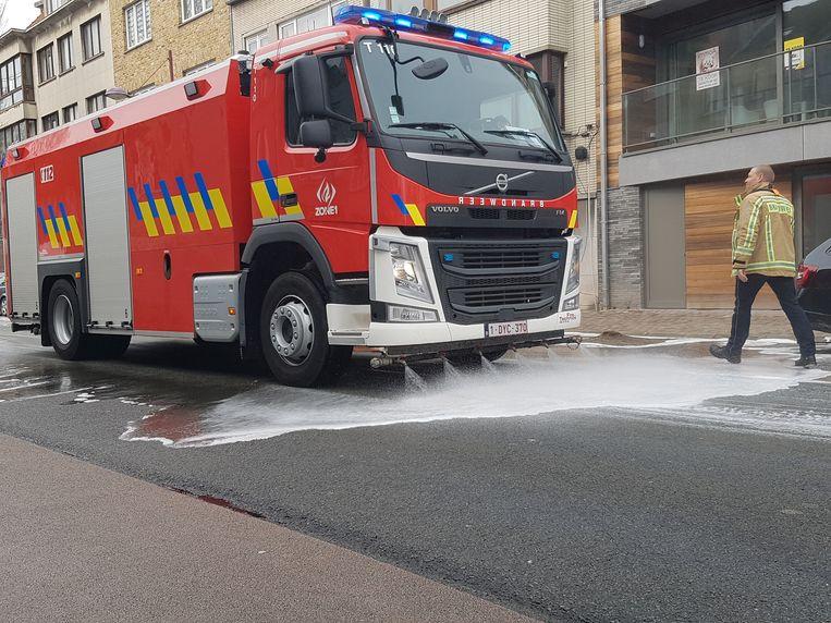 Illustratiefoto - De brandweer spuit een detergent op de rijbaan om een oliespoor op te lossen.