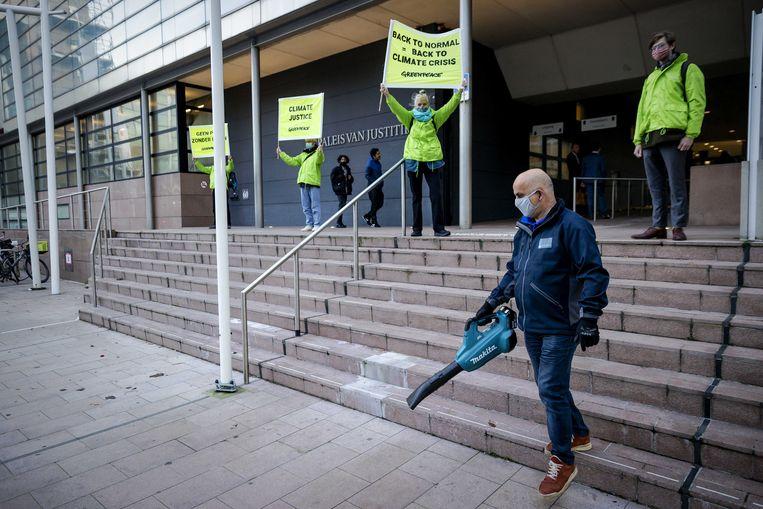 Medewerkers van Greenpeace staan met spandoeken bij de rechtbank voorafgaand aan het kort geding van de milieuorganisatie tegen de overheid. Beeld ANP