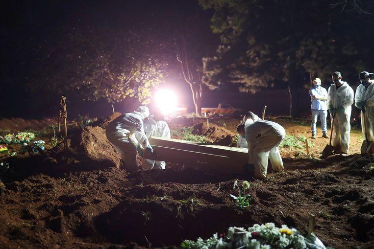 Ook 's nachts moeten de doden worden begraven in Brazilië. Beeld REUTERS