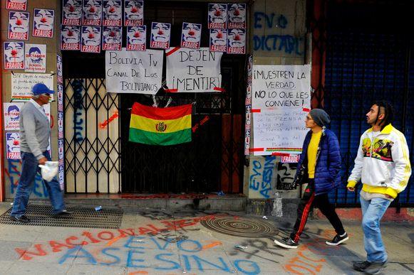 Voorbijgangers passeren de afgesloten ingang van Bolivia TV met affiches die president Evo Morales afschilderen als clown en met teksten als 'bedrieger', 'stop met liegen' en 'toon de waarheid en niet wat je uitkomt'.