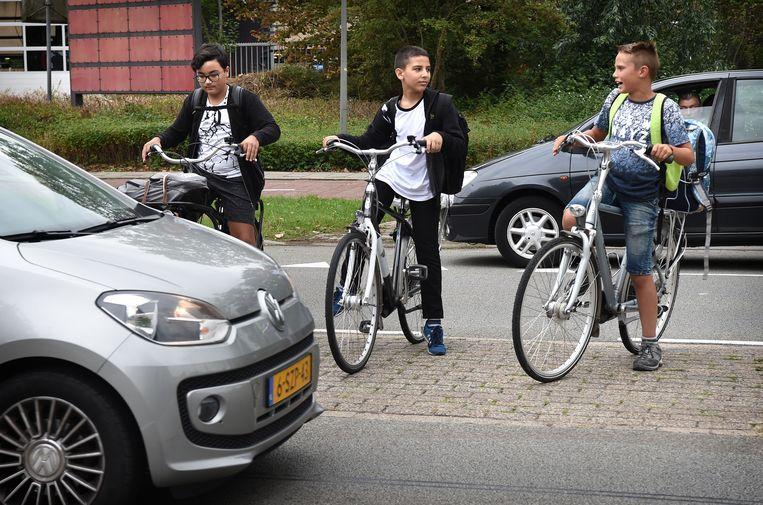Brugklassers in Arnhem hebben zojuist hun boeken gehaald op school en proberen de weg voor hun school over te steken. Beeld Marcel van den Bergh