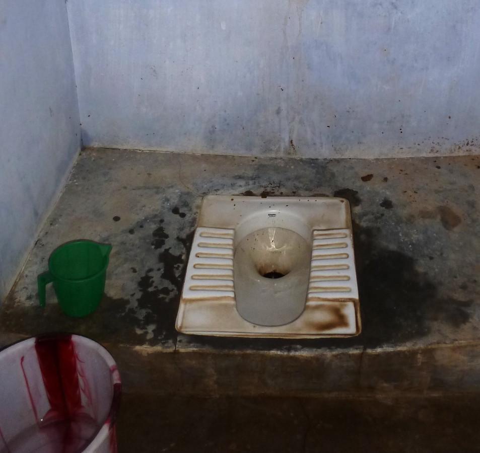 Een hurktoilet in het toiletgebouwtje van de school.