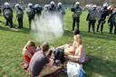 Vier jongeren in het Ter Kamerenbos tijdens het nep-festival La Boum. De politie trachtte het park te ontruimen en gebruikte daarbij onder meer traangas.