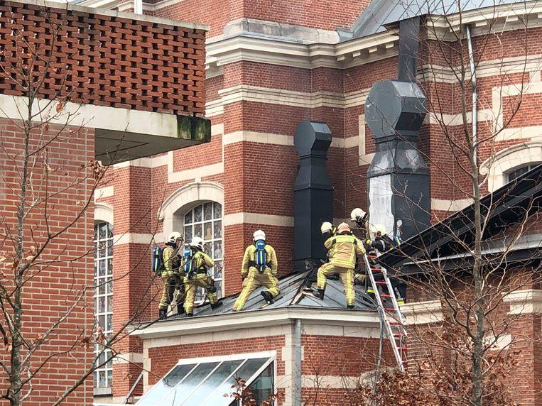 Brandweerlui aan het werk op het dak van The Jane.