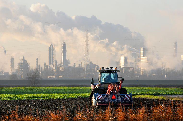 Zeeuwse boer bemest zijn land met op de achtergrond de chemische industrie van de Antwerpse haven en de kerncentrale van Doel. Beeld Hollandse Hoogte