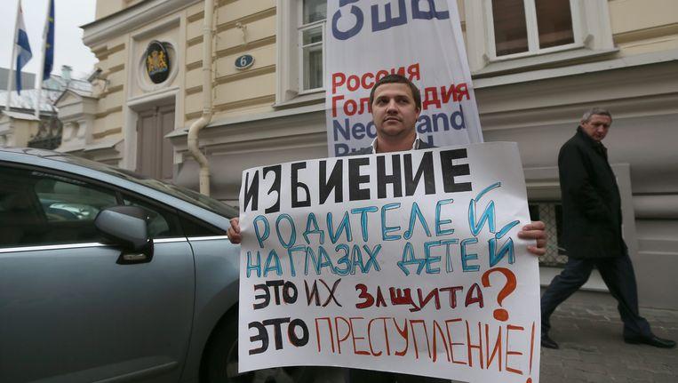 Een man met een bord voor de Nederlandse ambassade in Moskou. Op het bord: 'Ouders slaan voor de ogen van hun kinderen, is dat jullie bescherming? Dat is misdaad' Beeld EPA