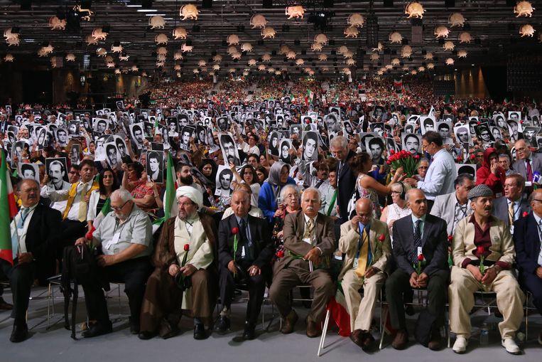 Mensen tonen op de Free Iran Rally 2018 in Villepinte portretten van familieleden die zijn omgekomen onder het Iraanse regime. Deze bijeenkomst van de Iraanse oppositiebeweging MEK was het doelwit van de bomaanslag, die op het nippertje werd verijdeld. Beeld AFP