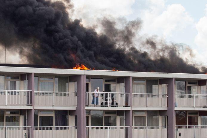 Deze dame wist net als andere bewoners veilig het complex te verlaten. De woningen bleven onbeschadigd, omdat de brand op het dak woedde.