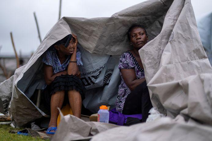 Ontheemde mensen proberen tevergeefs te schuilen voor de regen in een opvangkamp in Les Cayes, Haïti.