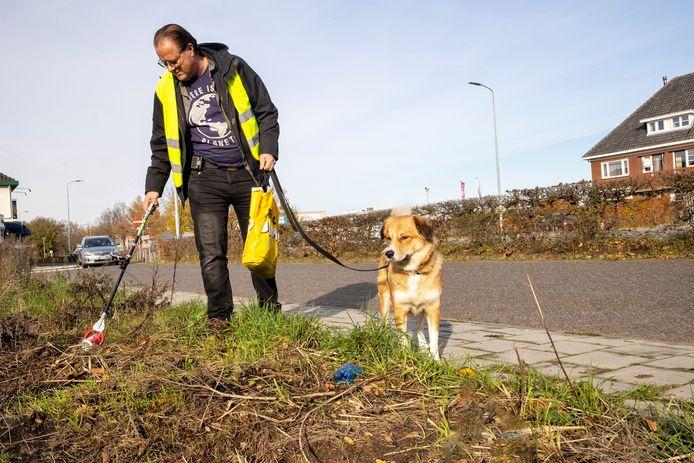 Guido Wilmes en zijn hond Nala rapen elke week zwerfafval in Acht. Aan de grijper zit een telefoon zodat de gegevens naar de database verstuurd worden.