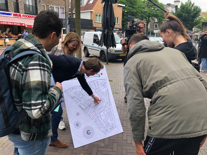 D66-fractievoorzitter Robin Verleisdonk wijst naar een plattegrond van Oud-Woensel tijdens een gesprek met bewoonster Beate Rybak (r)