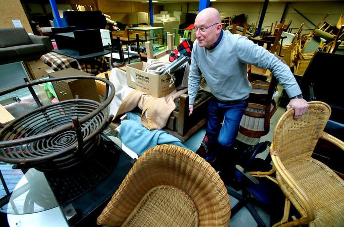 Directeur Marcel van Goch klautert over een stapel spullen in de kringloopwinkel.