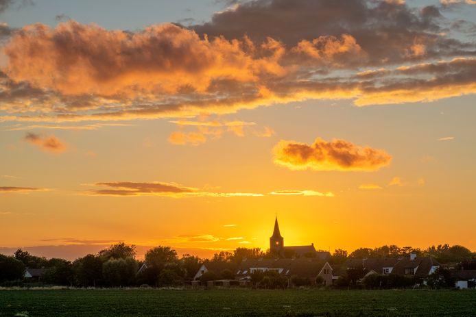 TRANSPARANTE KERK De ondergaande zon piept door de kerktoren van Noordwelle.