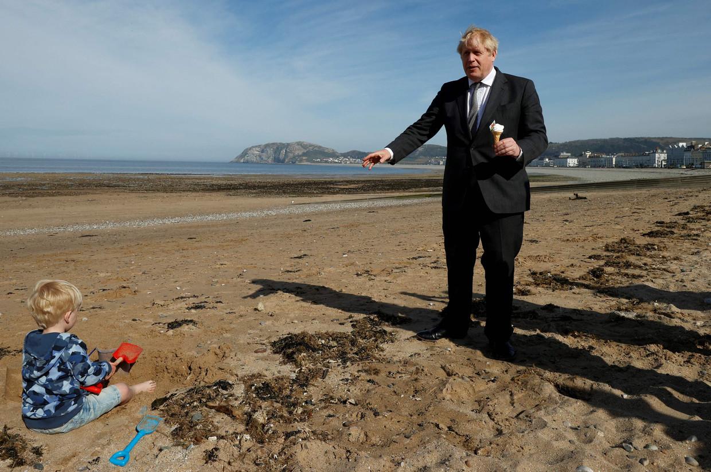 Brits premier Boris Johnson staat met een ijsje op het strand, tijdens zijn campagne in Wales. Beeld AFP