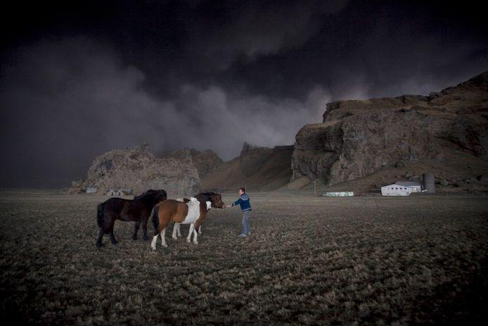 Archieffoto: een IJslandse kweker lokt zijn ijslanders naar de stal, na de uitbarsting  van de Eyjafjallajökull-vulkaan in april 2010. De vulkaanuitbarsting legde het Europese vliegverkeer dagenlang lam.